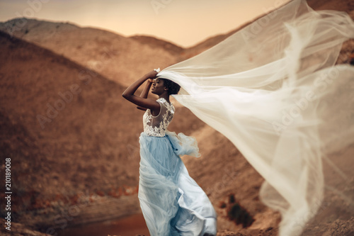 Canvas Print Black bride stands and holds waving bridal veil in her hands on background of beautiful landscape