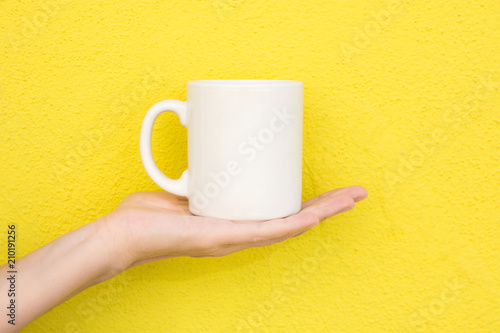 Young Caucasian Woman Holds on Hand Palm Blank Mockup White Mug on Bright Yellow Painted Wall. Airy Breezy Style. Template for Text Artwork Lettering. Trendy Minimalist Urban Atmosphere