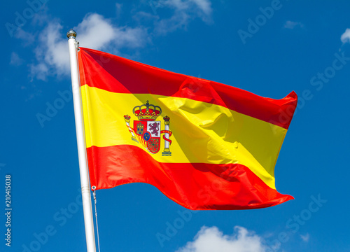 Wallpaper Mural Flag of Spain waving in the wind on flagpole against the sky with clouds on sunn