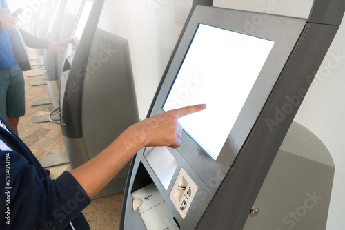 Asian boy check-in by using kiosk self check-in machines in Terminal at International Airport.