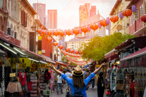 Canvas Print Young woman traveler with backpack and hat traveling into Chinatown at singapore city downtown