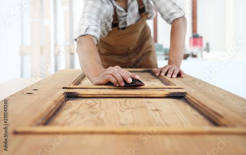 Stampa su Tela carpenter work the wood with the sandpaper