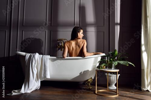 Foto Young beautiful woman sitting in bathroom near expensive bathtub bath looking at