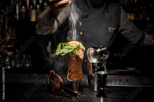 Bartender adding powder to a fresh summer cocktail with fruits