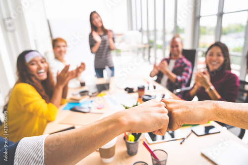 Photo Business partners or men coworkers fist bump in team meeting, multiethnic diverse group of happy colleagues clapping hands