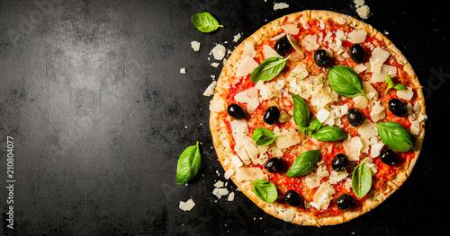 Fotografie, Obraz Traditional italian pizza on dark table