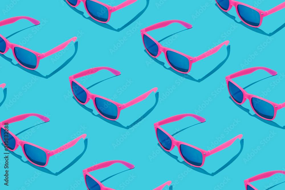 Pink sunglasses pattern on pastel blue background. Minimal summer concept.