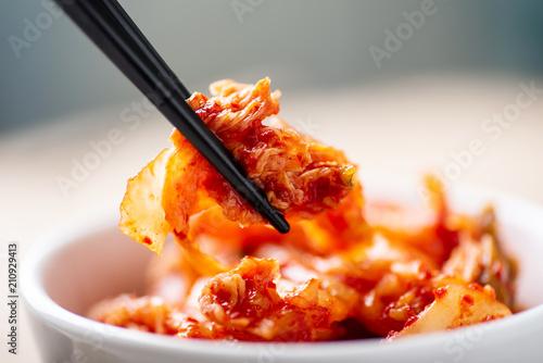 Hand holding chopsticks for eating kimchi cabbage, Korean food