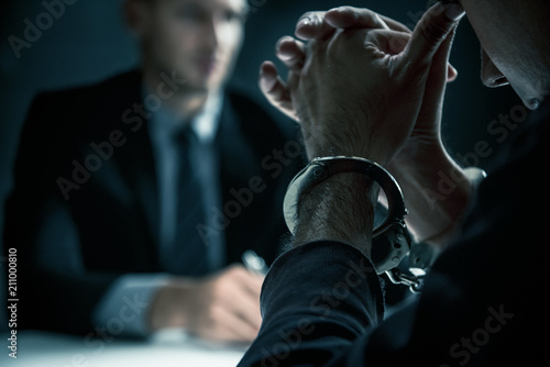 Fotomural Criminal man with handcuffs in interrogation room