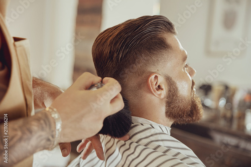 Barber shakes hair off from the client's neck.  Photo in vintage style