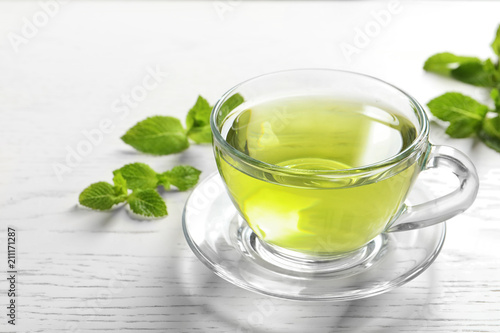 Cup with hot aromatic mint tea and fresh leaves on table