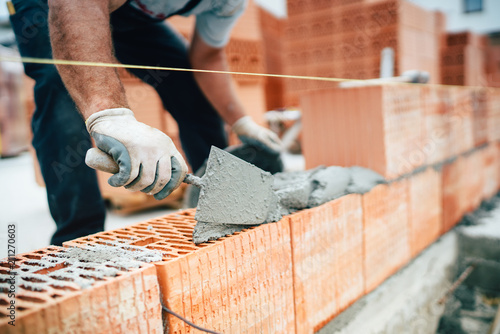 Vászonkép Professional worker using pan knife for building brick walls with cement and mor