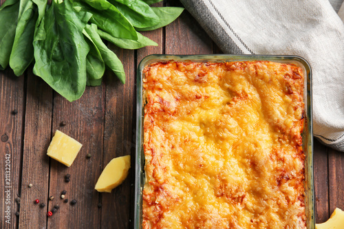 Delicious lasagna with spinach and cheese on wooden background