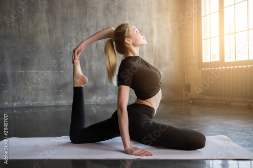 Athletic thin muscular young woman doing yoga practice in a loft studio, surrounded by bright sunlight. A girl meditating makes herself a healthy body and strengthening the spirit.