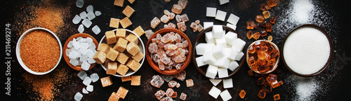 Set of different white and brown sugar in assortment, dark background, banner, top view
