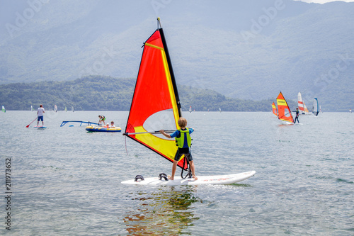 Little boy is learning how to windsurf in Domaso at Lake Como, Italy.