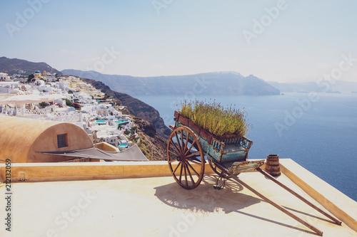 Nice vintage wooden cart with ocean coastline and village background