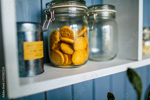 Fotografía Transparent jar of cookies on the wooden shelf in the kitchen