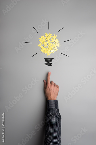 Hand of a businessman pointing on a light bulb made of yellow puzzle pieces