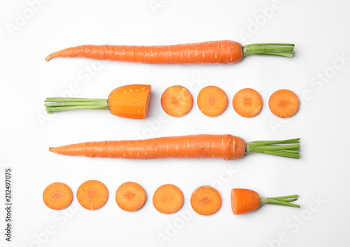Whole and cut fresh carrots on white background