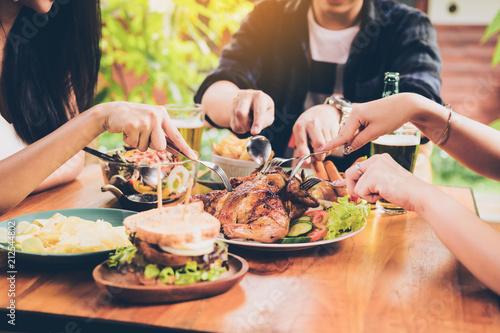 Asian friends enjoying eating turkey at restaurant.