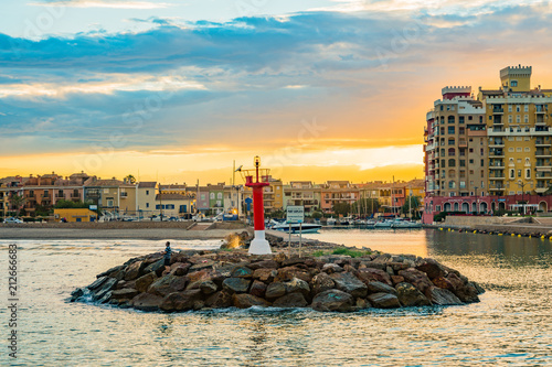 View of the lighthouse at the entrance to Port Saplaya Bay during a colorful sunset. Valencia
