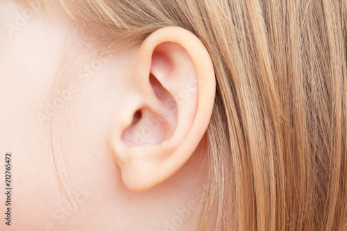 The little girl's ear is close-up. Isolated on white background. Fotobehang