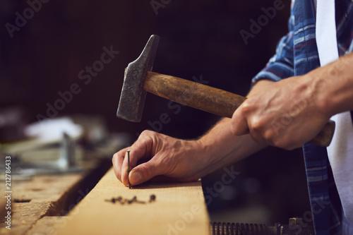 Obraz na plátne Carpenter hammering a nail into wooden plank in a carpentry shop