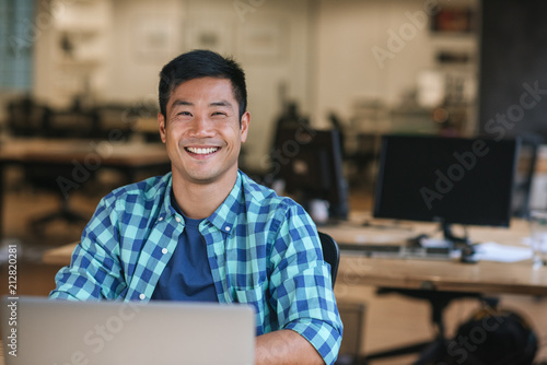 Smiling young Asian designer using a laptop at his desk