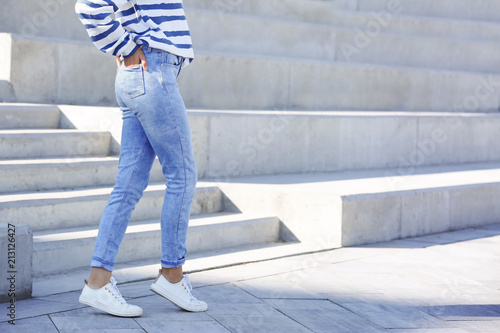 Young hipster woman in stylish jeans standing near stairs outdoors