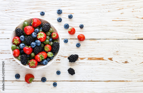 Obraz na plátně Fresh juicy ripe berries in a white plate-strawberries, blueberries, blackberrie