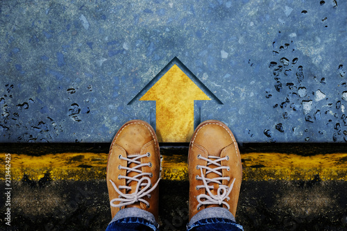 Motivation and Success Concept. Top View of Male with Leather Shoes satnding on the Crossroad to Making Decision to Steps or Stop. Forward Arrow on the Floor as background