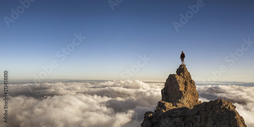 On the top of the world. Man on top of the mountain above the clouds.