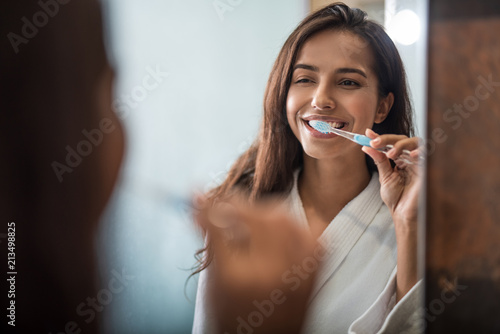 Fotografie, Obraz Portrait of beaming pretty woman brushing teeth while looking at mirror