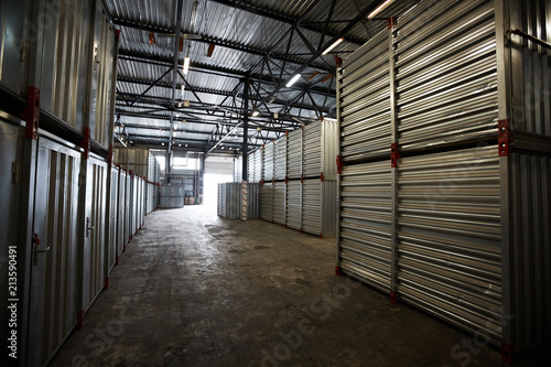 Canvas Print Dark cargo storage room with metal roof where stacking containers
