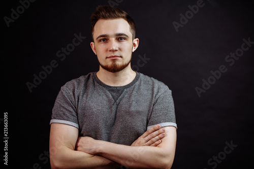 Photo Portrait of attractive young male in grey t-shirt standing with crossed arms isolated on black background