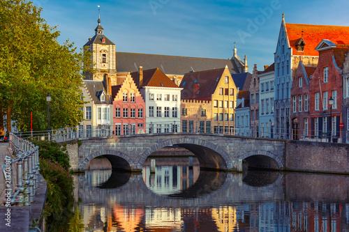Fototapeta premium Malowniczy widok na kanał Brugii z pięknymi średniowiecznymi kolorowymi domami, mostem i odbiciami wieczorem złotej godziny, Belgia