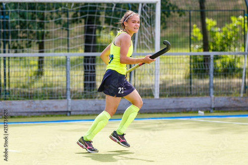 Young field hockey player girl with stick in the game