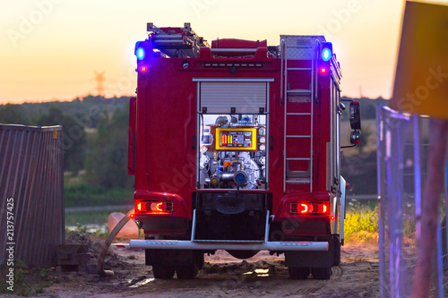 Canvas-taulu Flashing lights of red fire truck at dusk