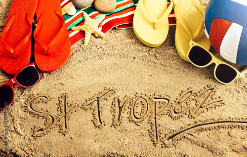 Summer concept of sandy beach, colorful thongs shoes, sunglasses, ball and inscr Fototapeta