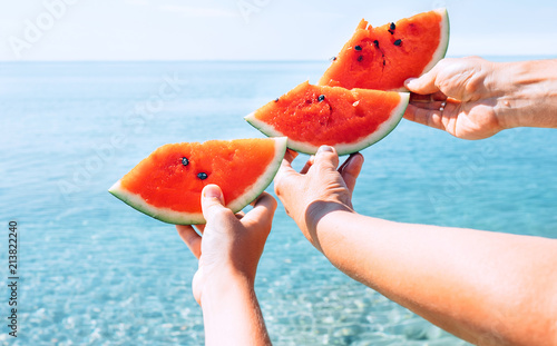 Three hands with watermelon segments are on azure calm sea water background