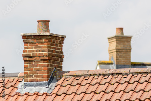 Fotografering Brick chimney stack on modern contemporary house roof top