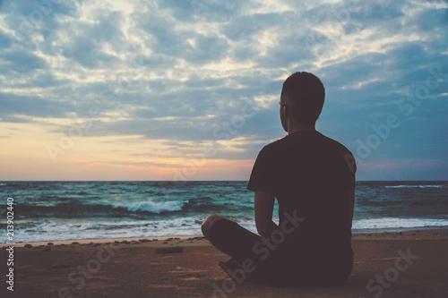 Fotografia, Obraz Young man meditating on top ocean cliff during sunset.