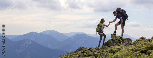 Young tourists with backpacks, athletic boy helps slim girl to clime rocky mountain top against bright summer sky and mountain range background. Tourism, traveling and healthy lifestyle concept.