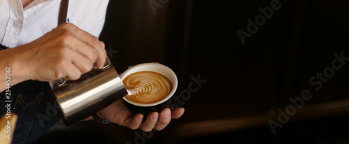 Branner of barista hand making a cup of coffee.
