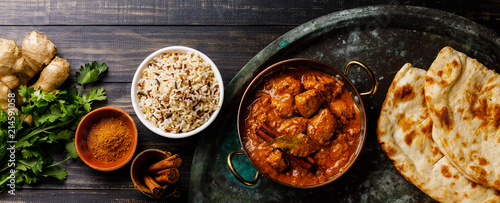 Valokuva Chicken tikka masala spicy curry meat food with rice and naan bread on dark back