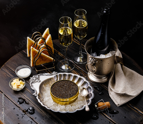 Black caviar on ice in silver bowl, fresh bread toast and champagne in ice bucket on dark background