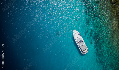 Luxury small yacht anchoring in shallow water