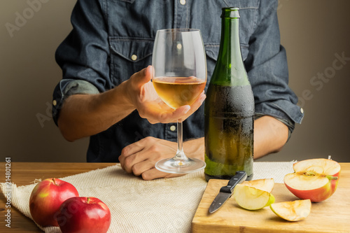 Photo Beautiful ice cold glass and bottle of apple wine, with ripe apples in background