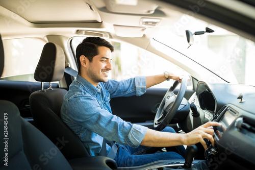 Photo Man switching radio station while driving